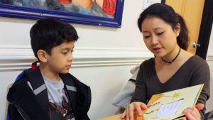 A volunteer tutoring a child