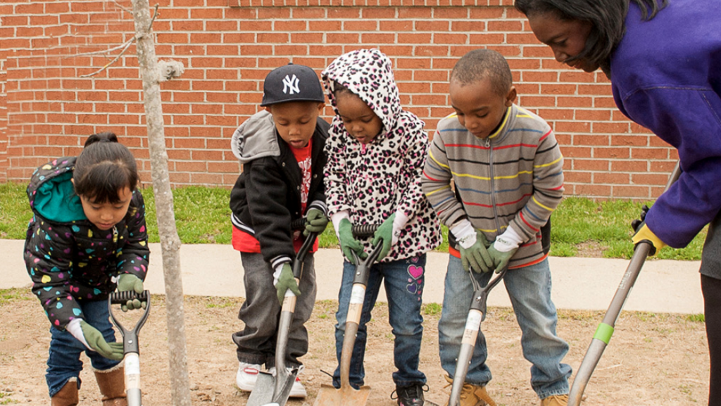 Children helping to plant a tree
