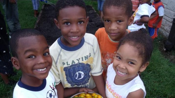 A group of children posing with tomatoes